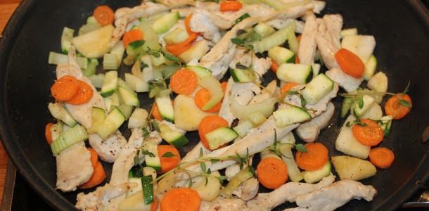 Kyllingen og grøntsagerne steger på panden